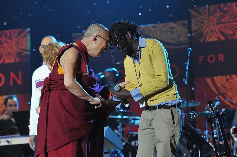 SYRACUSE, NY - OCTOBER 09: His Holiness the Dalai Lama speaks with Emmanuel Jal onstage at the One World Concert at Syracuse University on October 9, 2012 in Syracuse, New York. (Photo by Larry Busacca/Getty Images for Syracuse University)
