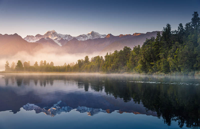 Mount Cook and Mount Tasman reflected in Lake Matheson Sunset New Zealand