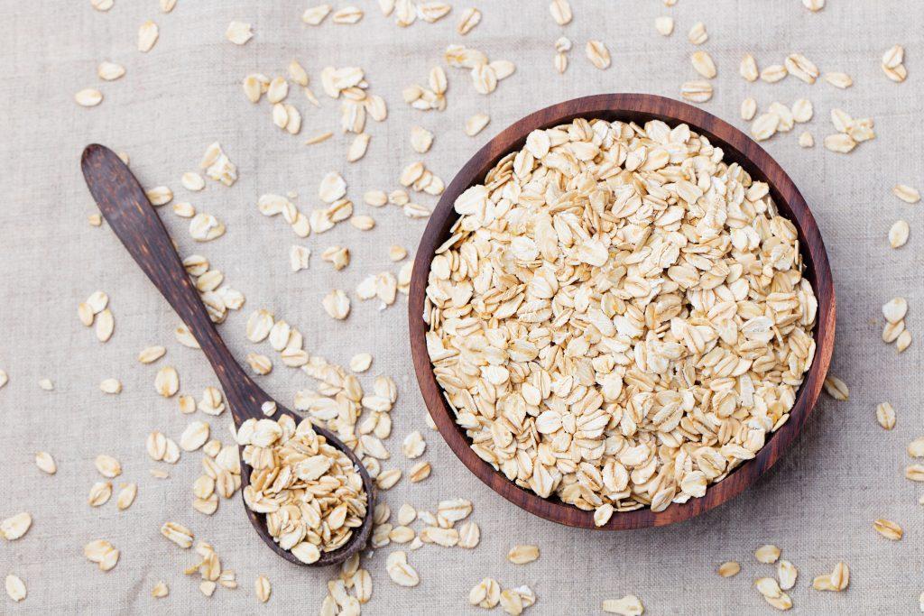 Prebiotics vs. Probiotics: Bacteria and Gut Health Oat Flakes Wooden Bowl Spoon