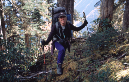 christine boskoff on a hike with polls and backpack smiling mountain