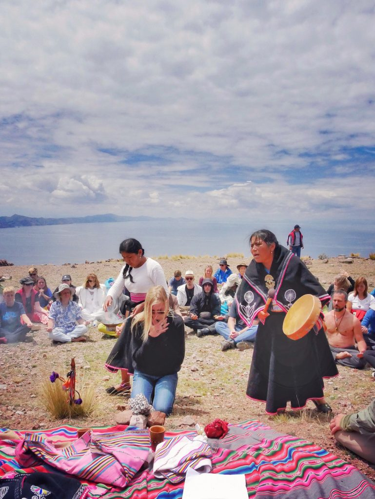 Local wisdom keepers from Raqchi perform traditional ceremony atop Isla Amantani Peru