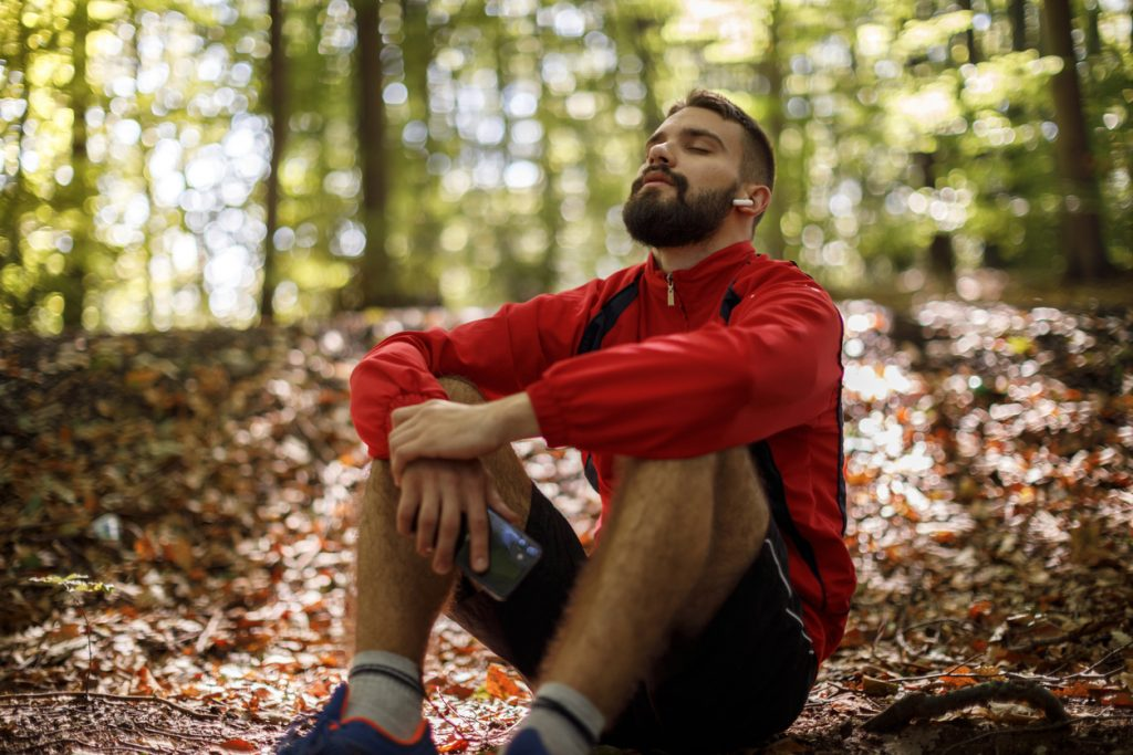 mindful meditation in the forest young man breathes and listens to music on Bluetooth headphones